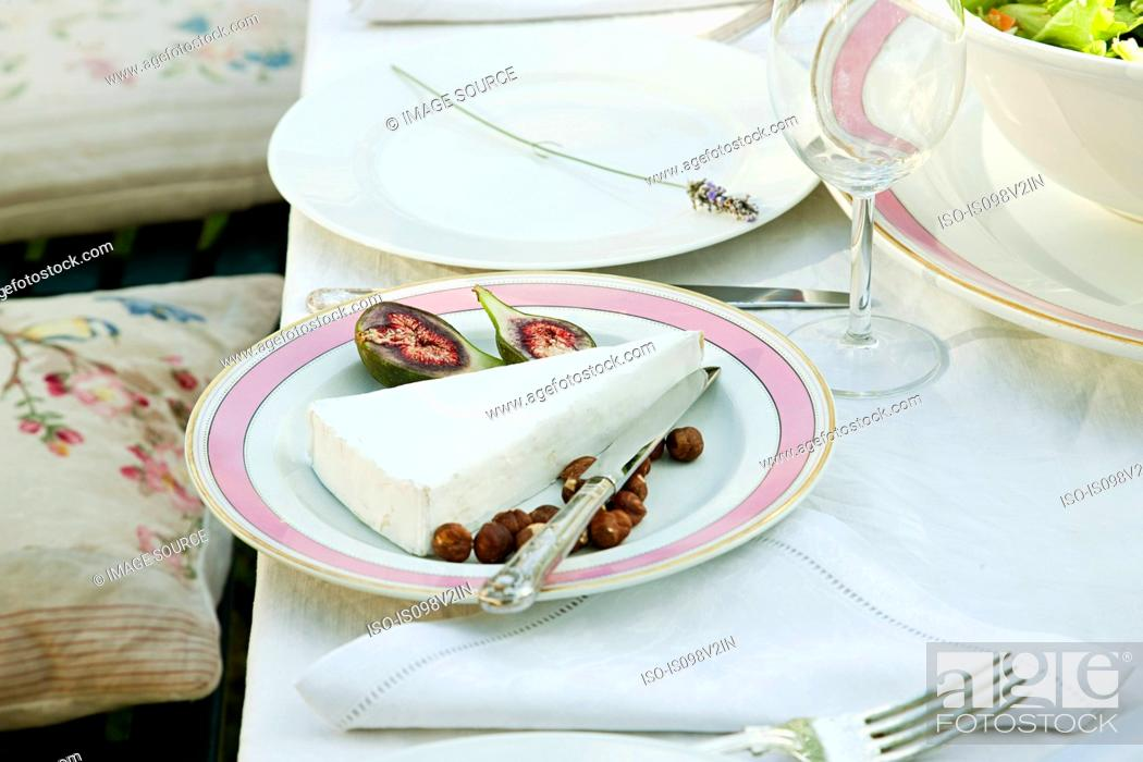 Stock Photo: Plate of cheese, figs and hazelnuts.