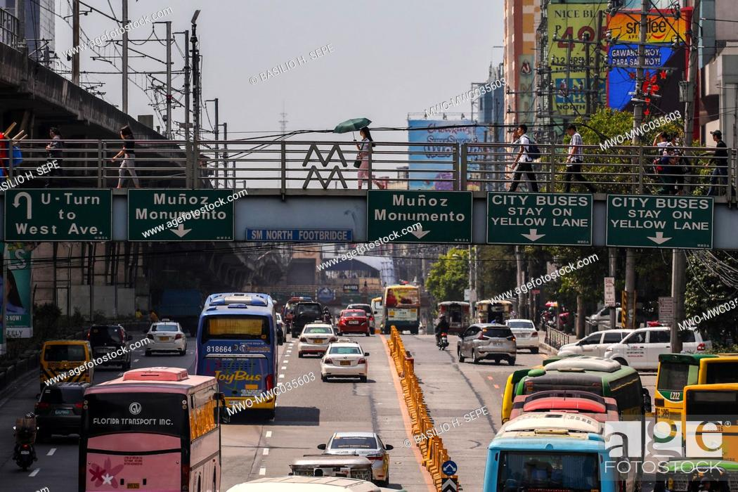 Imagen: People walk on a pedestrian bridge along a major road. The Philippine economy plunged into recession on as it grapples with surging coronavirus infections.