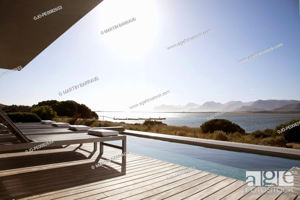 Stock Photo: View of sun shining on lake from patio with swimming pool.