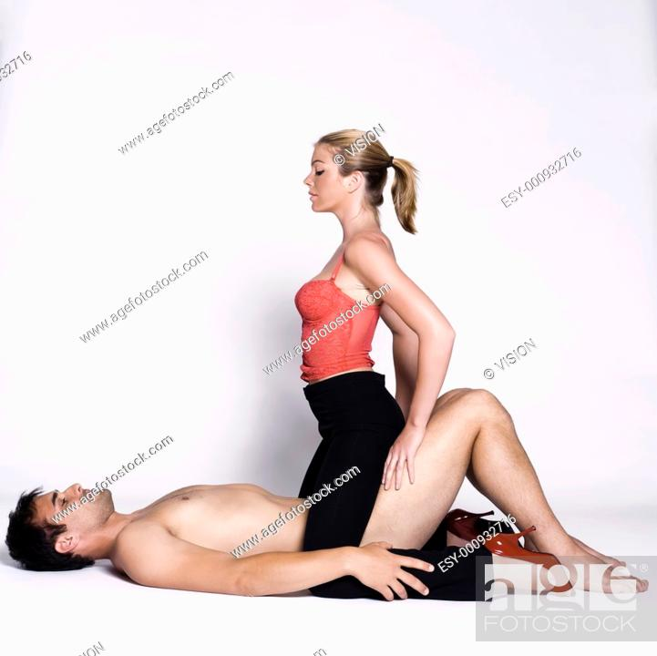 Stock Photo: young couple lying down with woman on top and man naked in studio on isolated grey background.