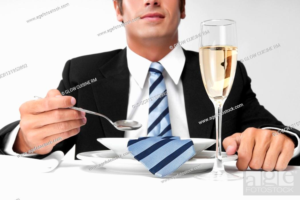 Stock Photo: Close-up of a businessman with his tie in a soup bowl.