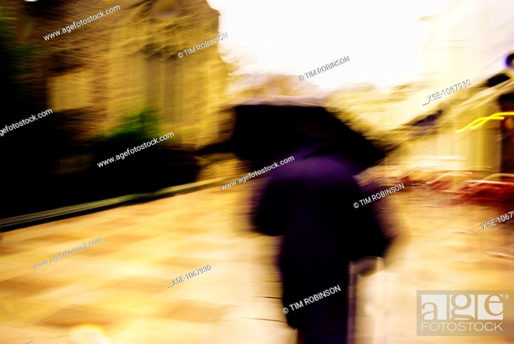 Stock Photo: Rearview adult with umbrella walking down wide city street in the rain, motion blurred.