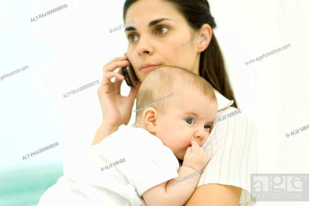 Stock Photo: Mother holding infant, using cell phone.