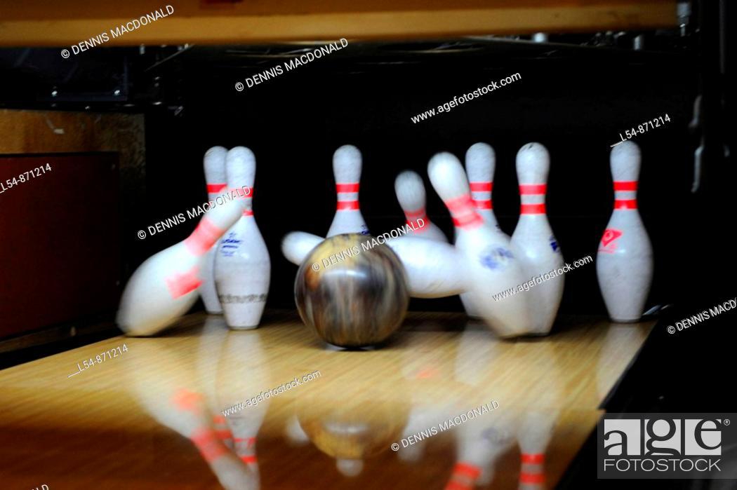 Stock Photo: Black Bowling Ball Hitting White Bowling Pins.