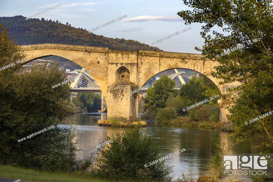 Stock Photo: Roman bridge in Ourense (Galicia, Spain), over river Miño and Millenium bridge in the background.
