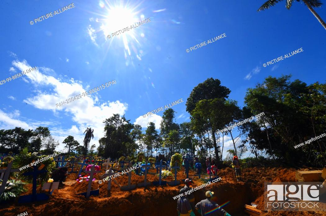 Stock Photo: 29 April 2020, Brazil, Manaus: The sun shines over a grave in which several coffins are lying in the middle of the Corona pandemic.
