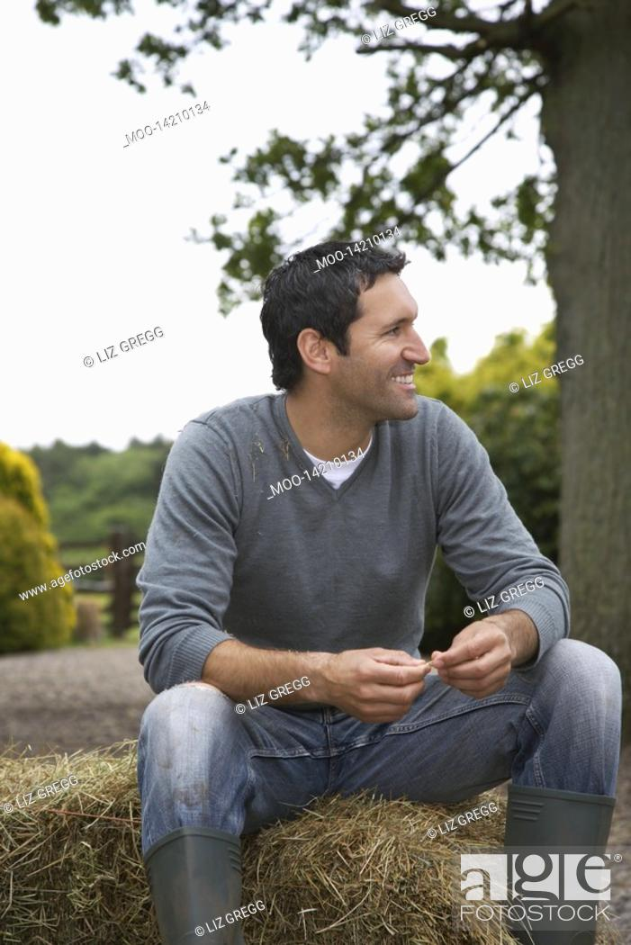 Stock Photo: Man sitting on hay bale in countryside.