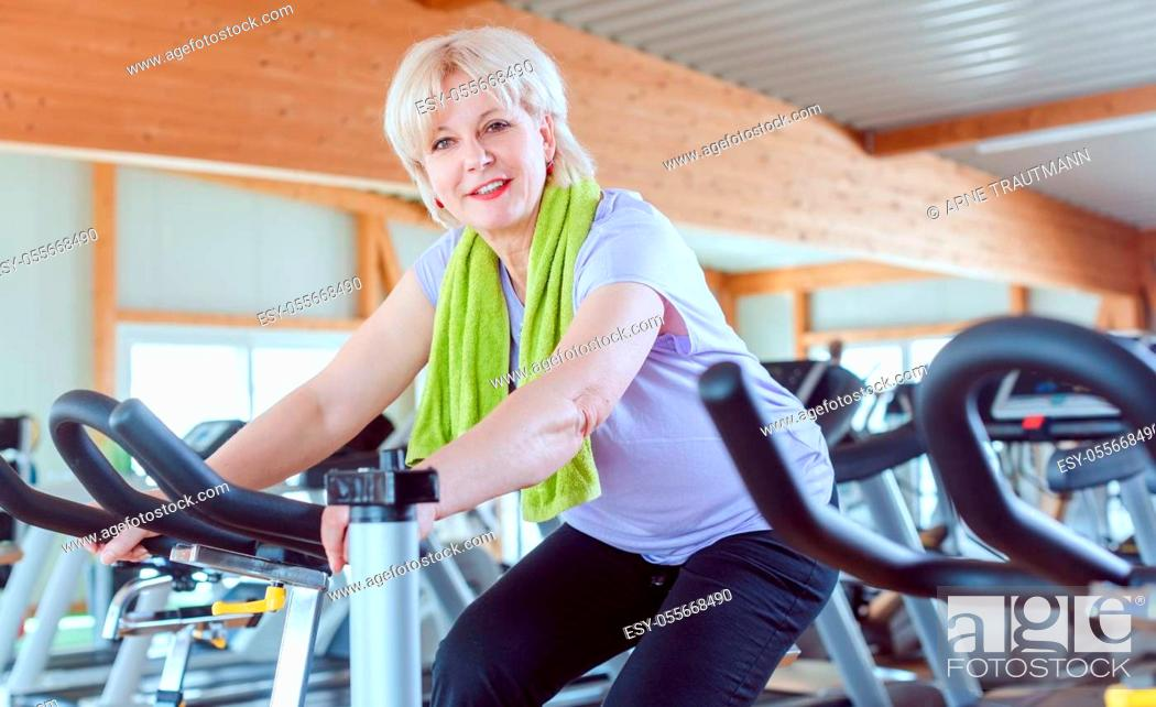 Stock Photo: Senior woman exercising for better fitness on a bike in a modern gym.