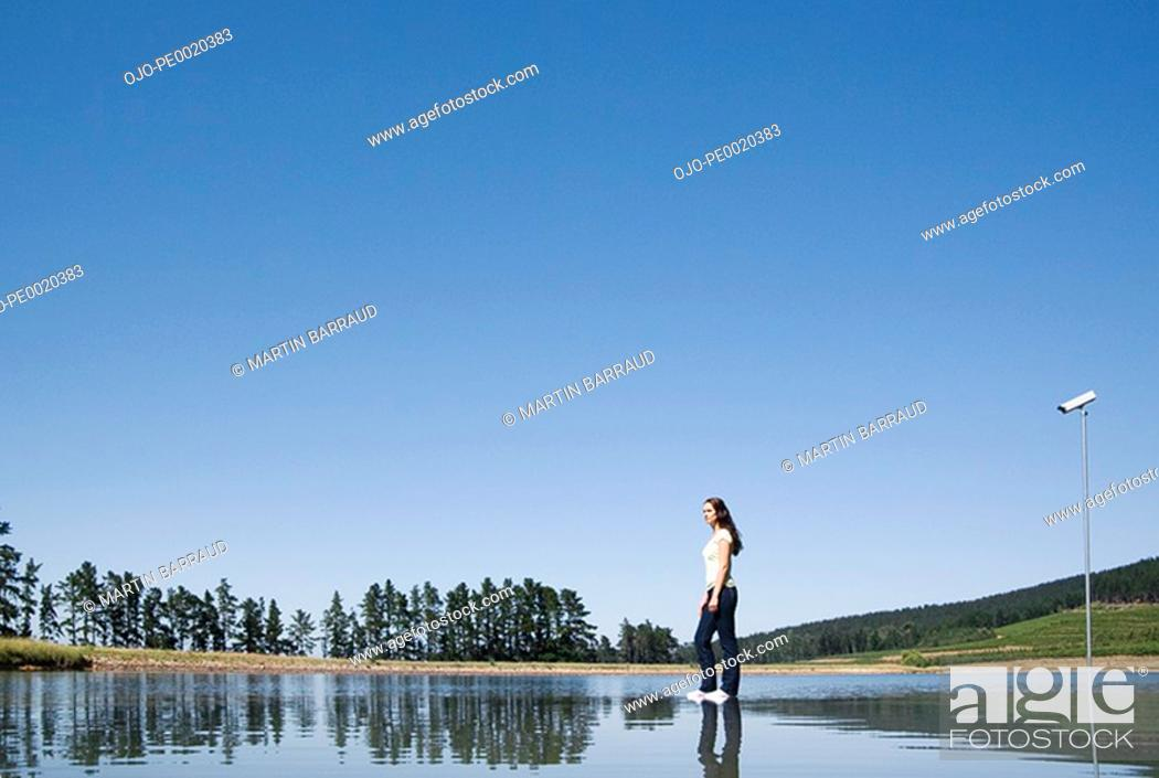 Stock Photo: Woman standing on water with surveillance camera and trees.
