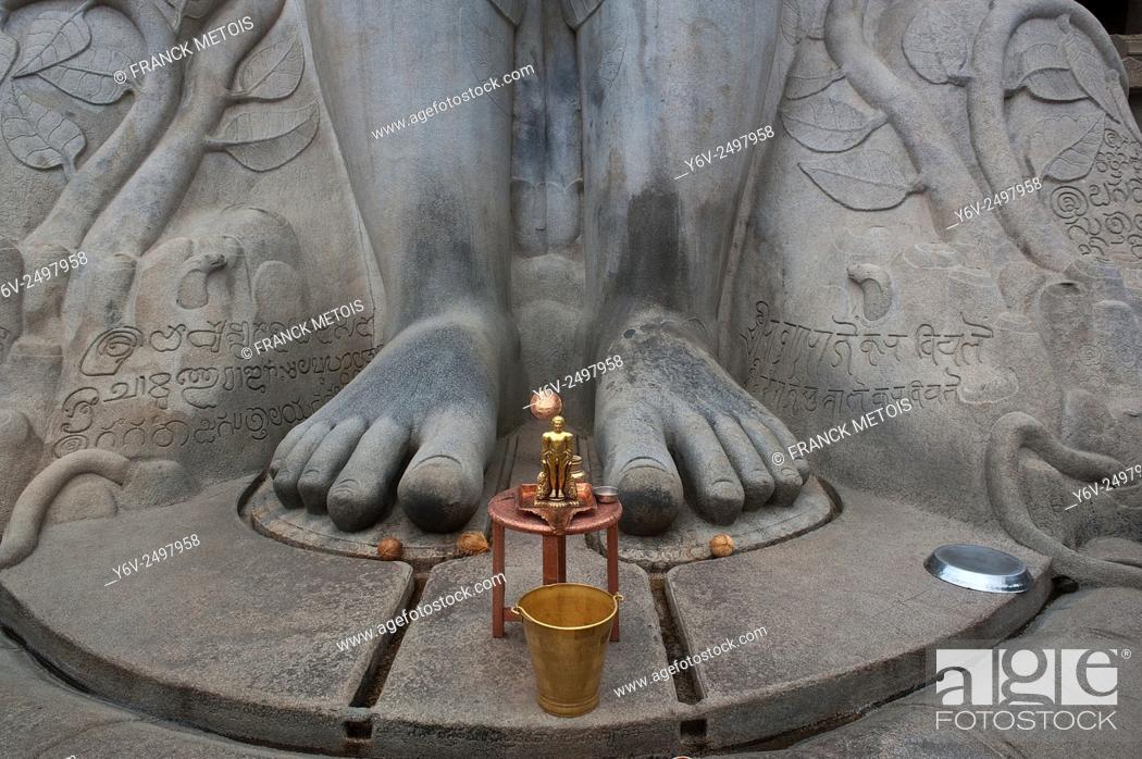 Stock Photo: A small statue representing a jaïn spiritual leader 'tirthankara' is at the feet of the statue of Gomateshvara one of the jaïn spiritual leader.