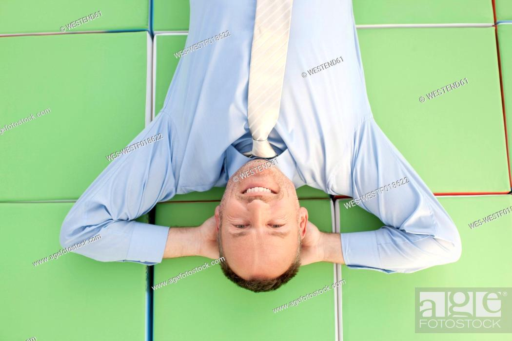 Stock Photo: Germany, Leipzig, Businessman resting on cubes, smiling, portrait.