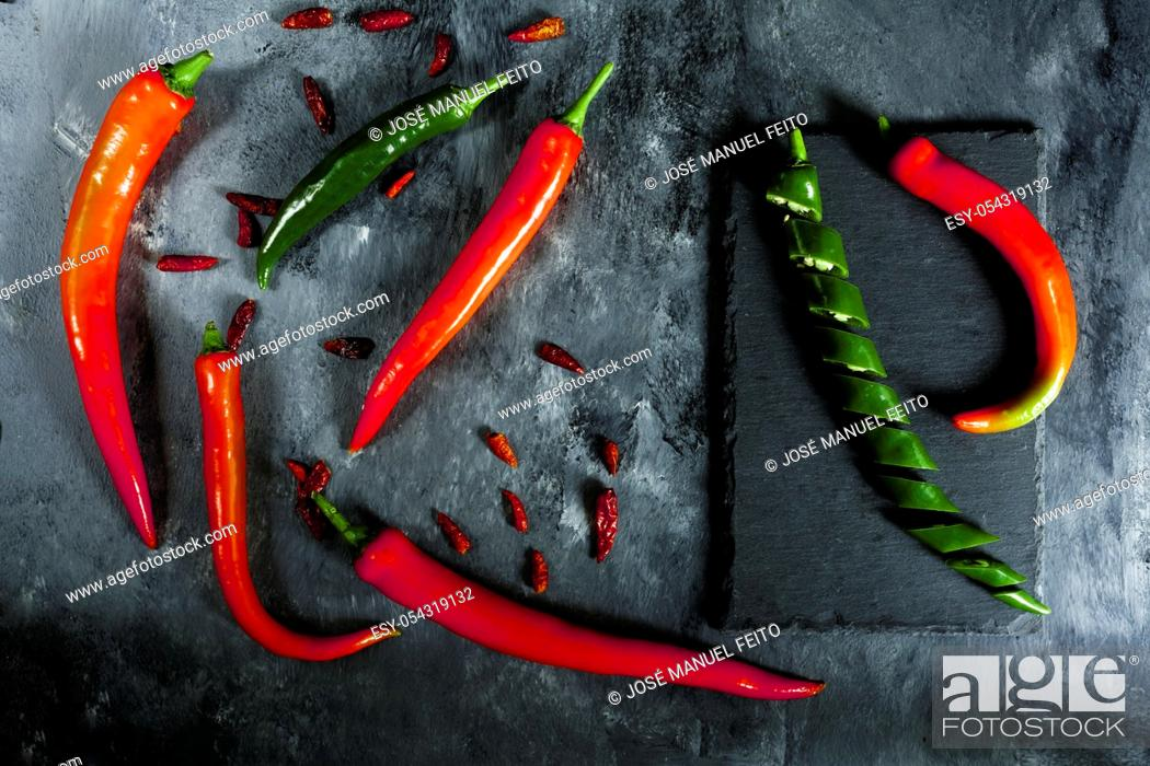 Stock Photo: fresh spicy green pepper sliced on slate, various fresh red spicy peppers and cayenne peppers on dark background from above. Top view.