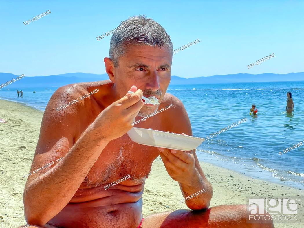 Stock Photo: Man on the beach having fast food lunch. Vacation time.