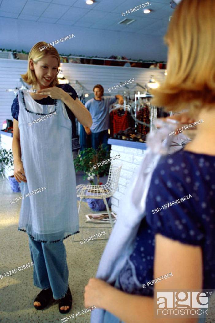 Stock Photo: Young woman trying on clothes in a clothing store.