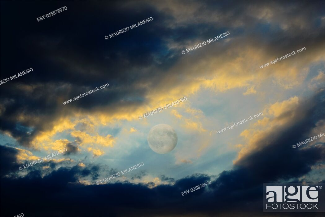 Stock Photo: After a violent thunderstorm, between dark clouds still full of rain, backlit by sunset, there is the full moon.