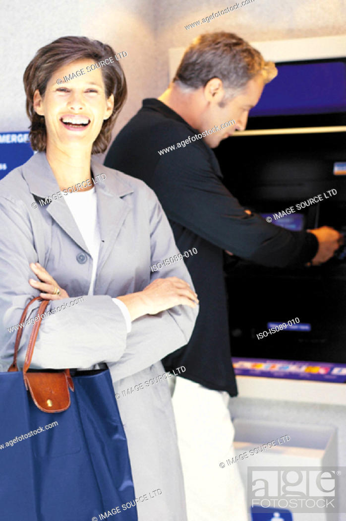 Stock Photo: Man and woman withdrawing cash.