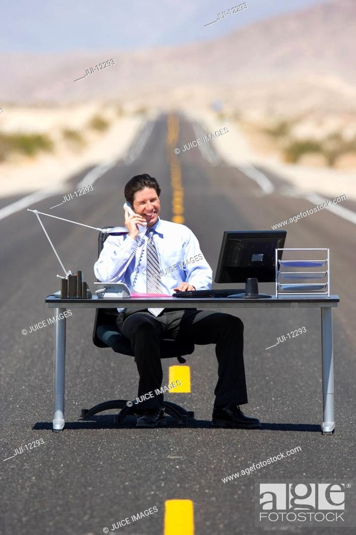 Stock Photo: Businessman at desk in middle of road in desert, using telephone.