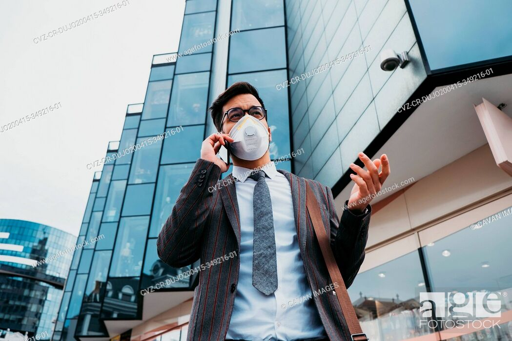 Stock Photo: Business man with protective face mask using phone on city street.