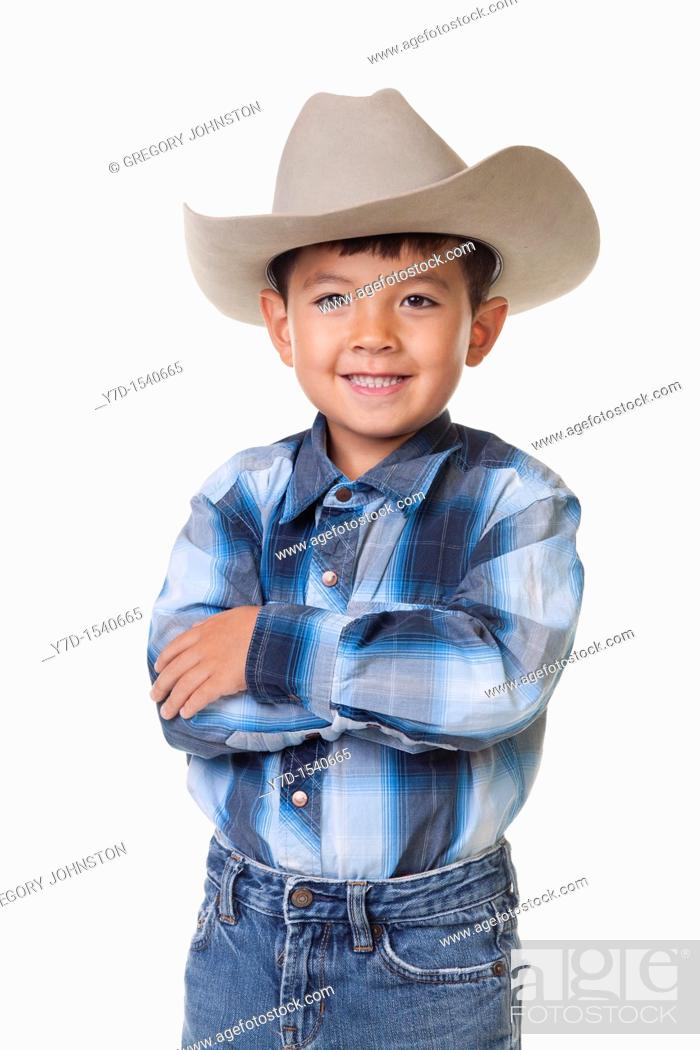 Stock Photo: A young boy in cowboy clothes crosses his arms and shows a big smile.