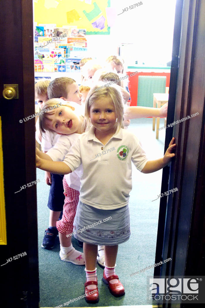 Stock Photo: Group of 2-4 year old children standing in the doorway of the classroom at nursery.