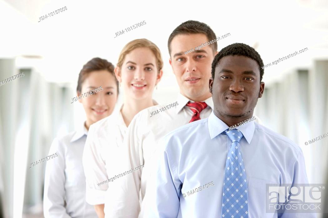 Stock Photo: Business people standing in a row and smiling at the camera together.