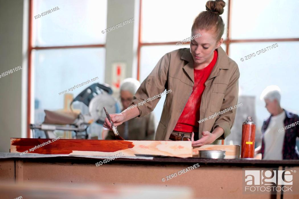 Stock Photo: Young female carpenter painting wood stain in furniture making workshop.