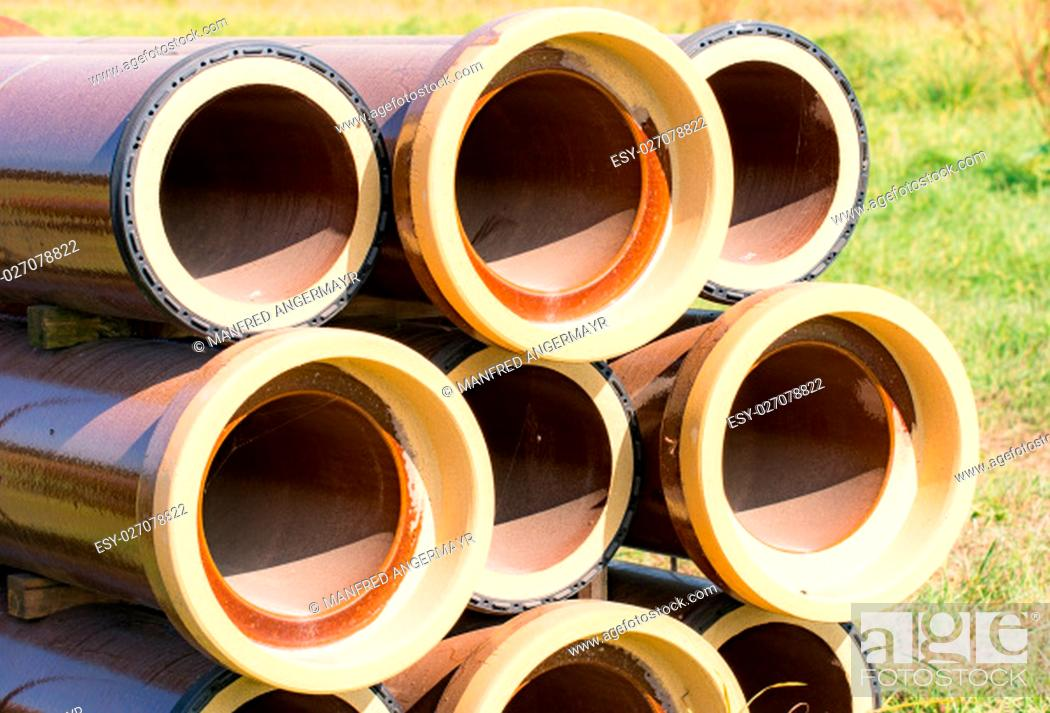 Stock Photo: Stack of canalization pipes at a construction site.