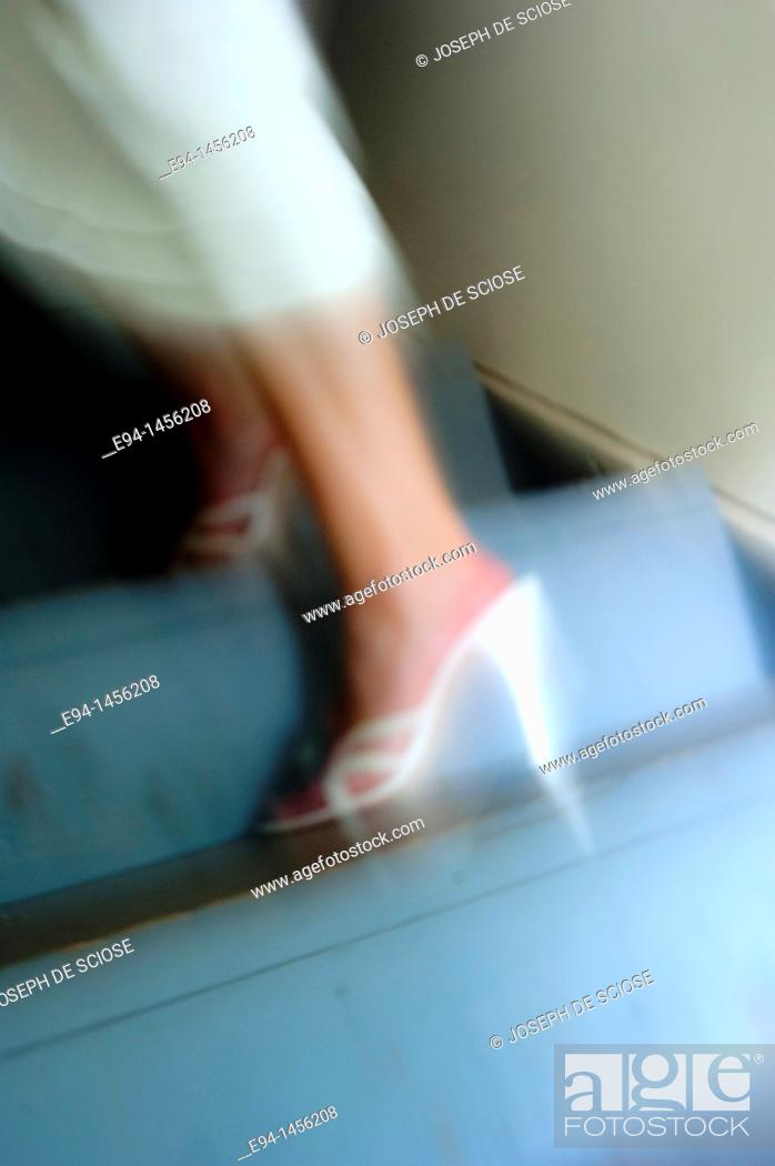 Stock Photo: Blurry woman's legs in heels and white dress on a stair way.
