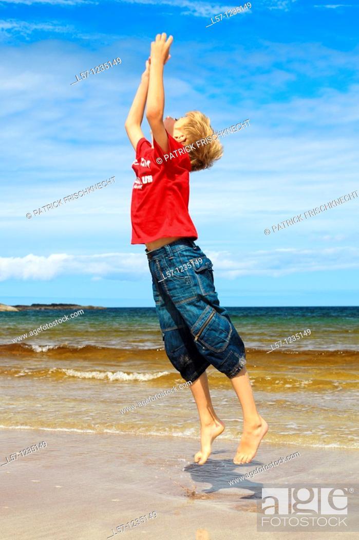 Stock Photo: boy running on sandy beach, Sutherland, Scotland.