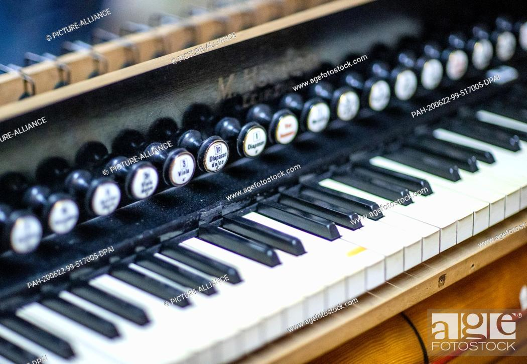 Stock Photo: 22 June 2020, Mecklenburg-Western Pomerania, Rostock: The keyboard of a reed organ made by M. Hörügel (Leipzig) in the 1930s is being restored in the workshop.