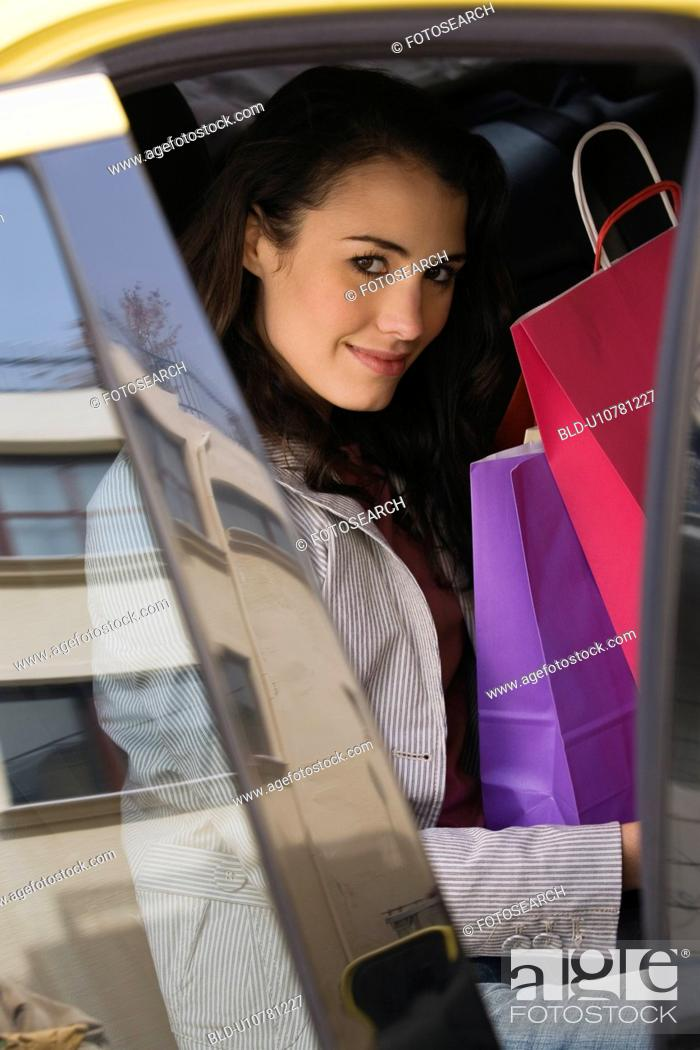Stock Photo: Woman with shopping bags in a taxi.