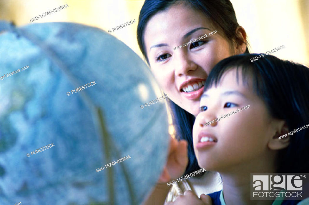 Stock Photo: Mother and her daughter looking at a globe.