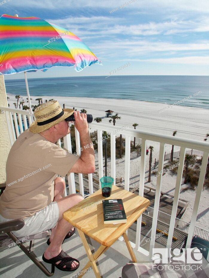 Stock Photo: Elderly man looking through binoculars from his balcony.