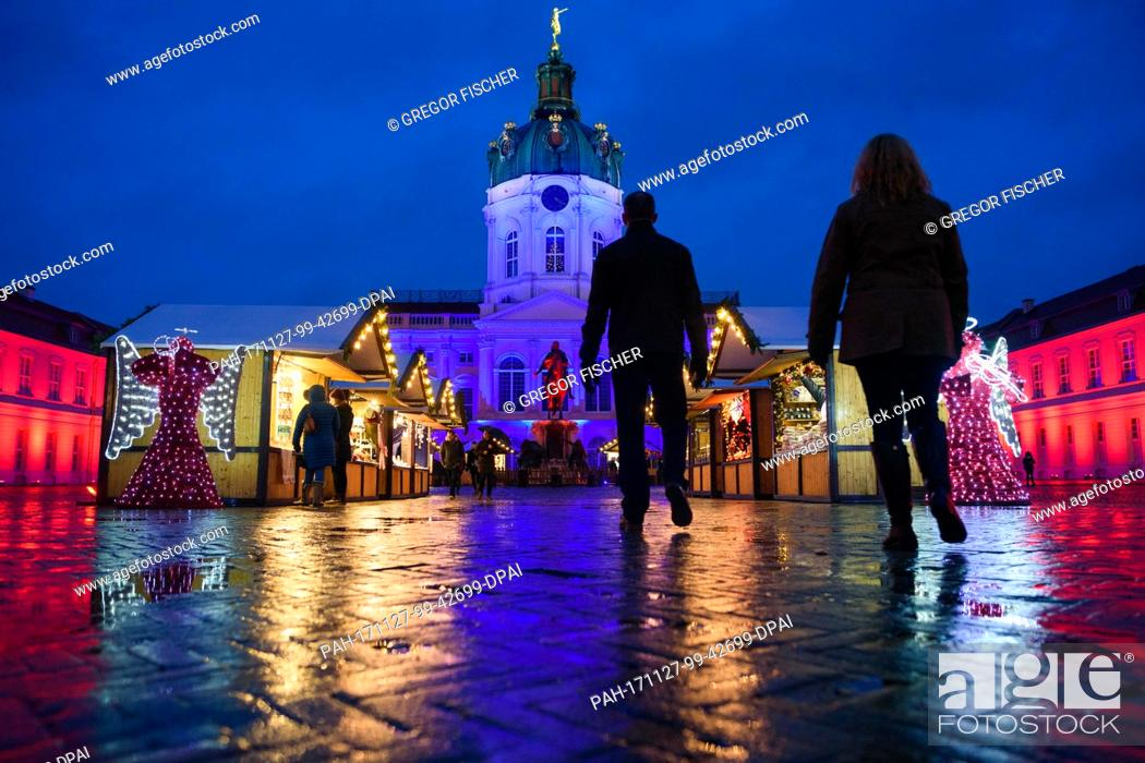 Stock Photo: Visitors walk the grounds of the Christmas market in the rain in front of Charlottenburg Palace, which is illuminated in various colours, in Berlin, Germany.