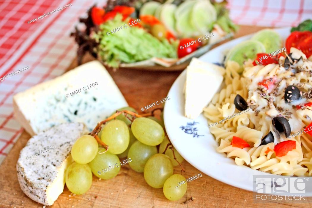 Stock Photo: Fusilli with white mushroom sauce  White mushroom sauce with fresh basil and thyme, tomato, black olives and leeks  Shrimp edges the plate  Red and green grapes.