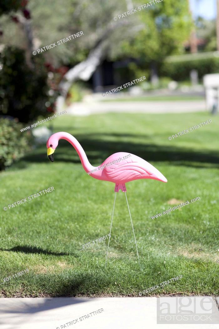 Stock Photo: A plastic pink flamingo stuck in a lawn, close-up.