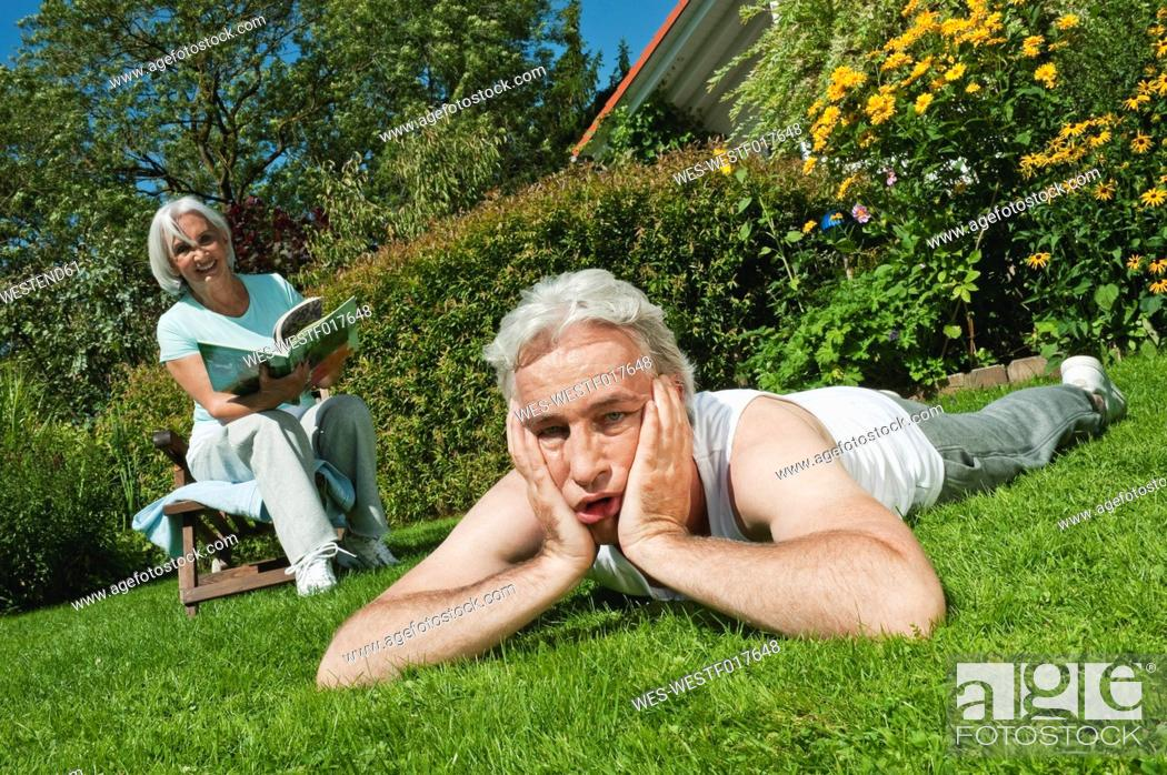 Stock Photo: Germany, Bavaria, Man tired and woman reading magazine in garden, smiling.