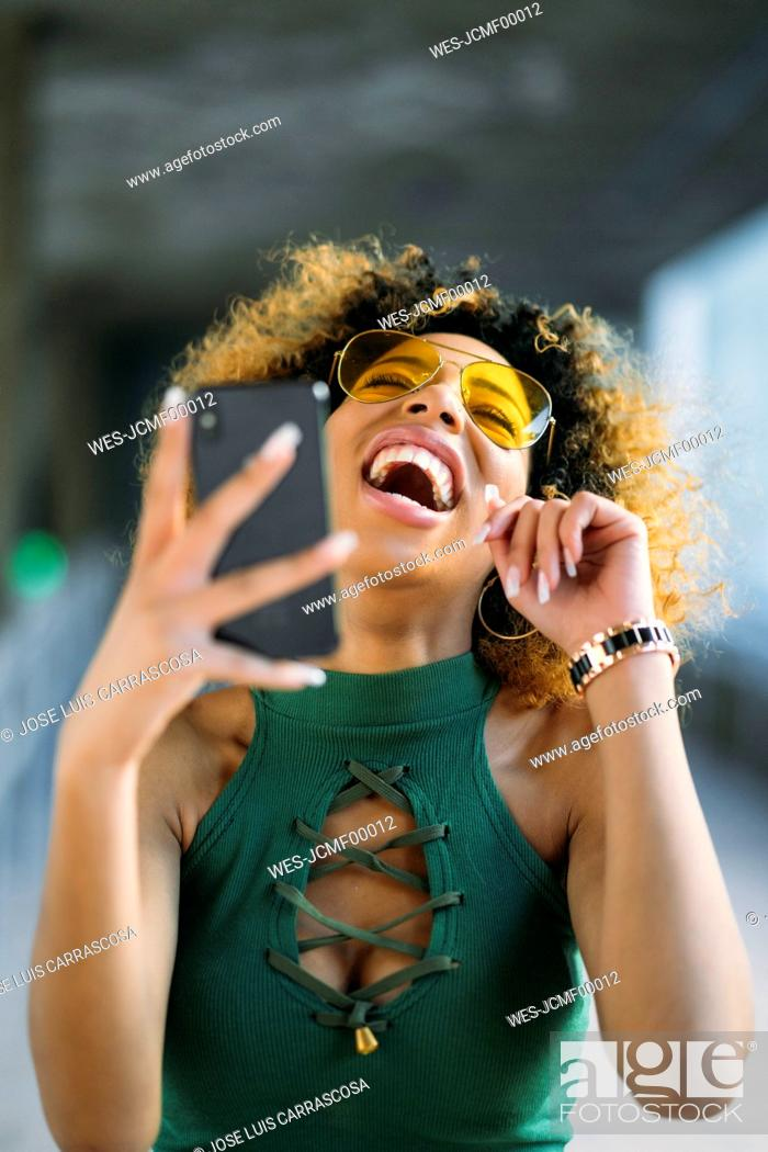 Stock Photo: Portrait of laughing young woman with smartphone outdoors.