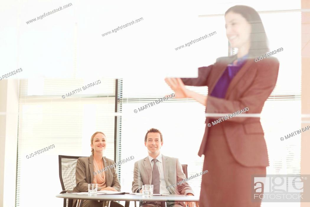 Stock Photo: Businesswoman leading meeting on visual screen in conference room.