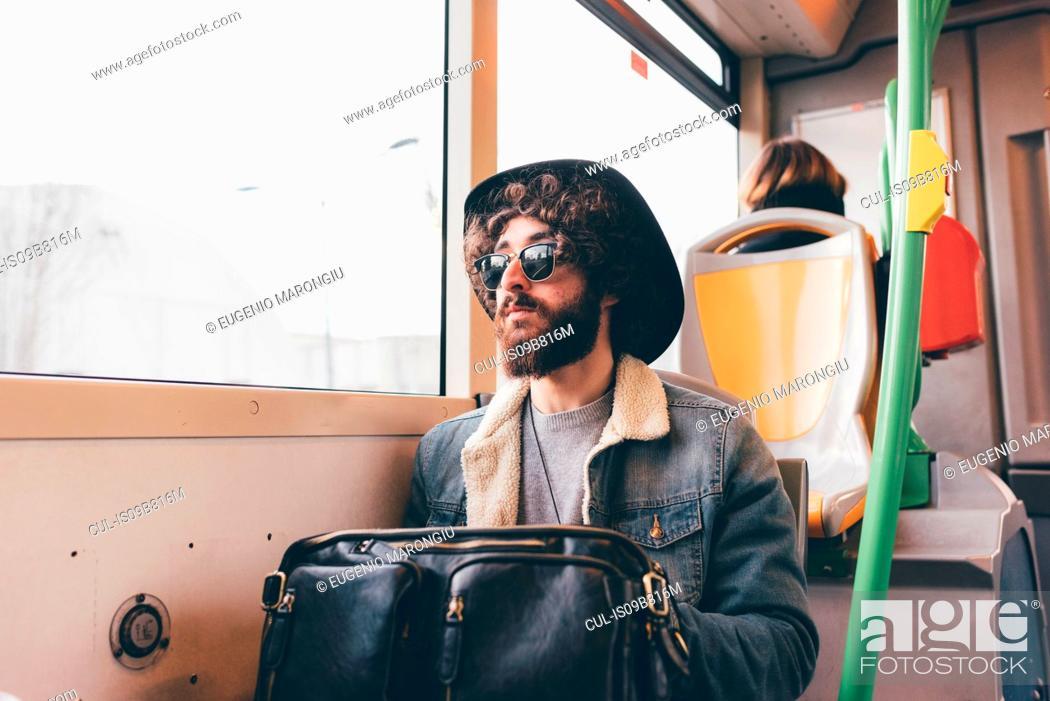 Stock Photo: Young man sitting on subway train.