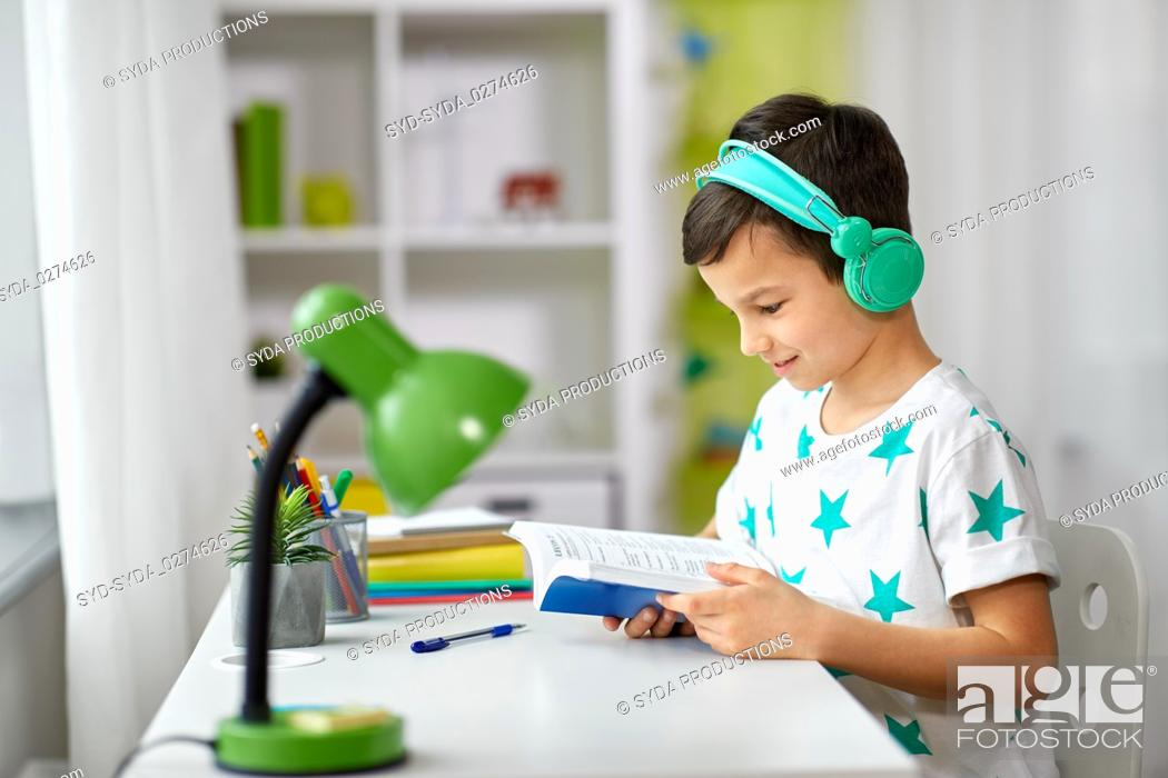 Stock Photo: boy in headphones with textbook learning at home.