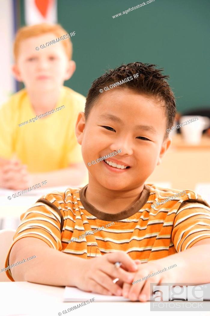 Stock Photo: Portrait of a schoolboy smiling in a classroom.