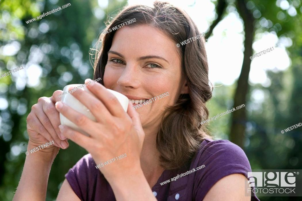 Stock Photo: Germany, Hamburg, Woman holding cup of coffee, portrait, close-up.