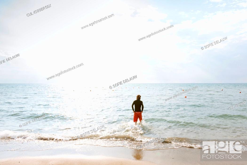 Imagen: Man standing at edge of sea.
