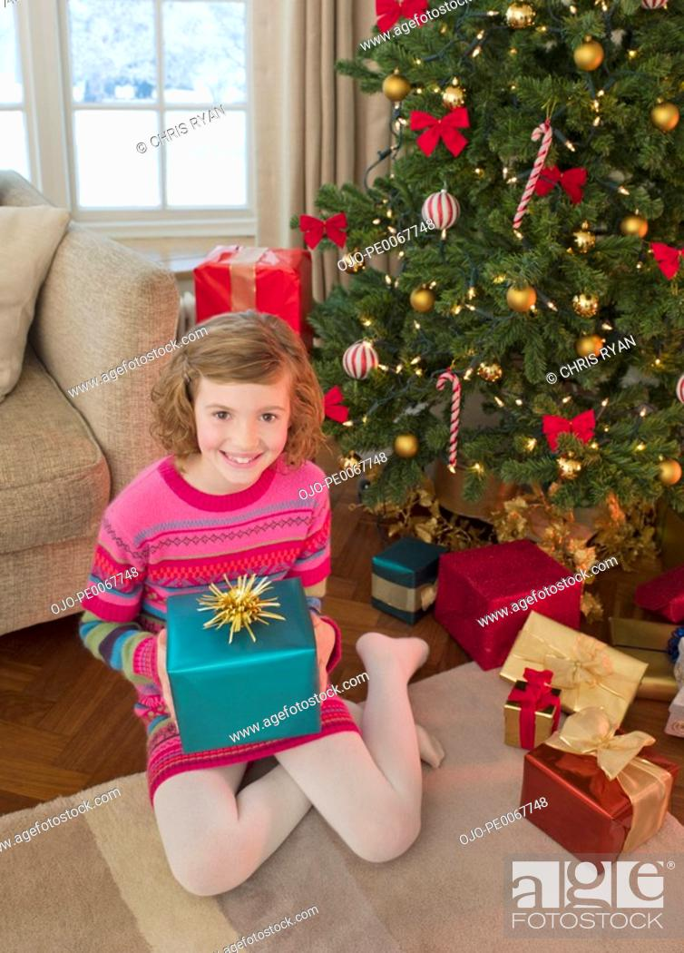 Stock Photo: Girl holding gift by Christmas tree.