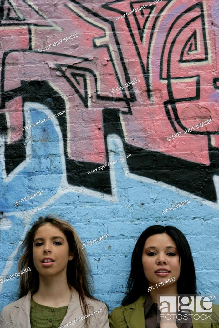 Stock Photo: Portrait of two women near a wall.