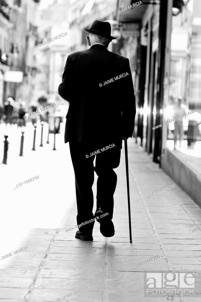 Stock Photo: Elderly man elegantly dressed walking down a street, Granada Spain.