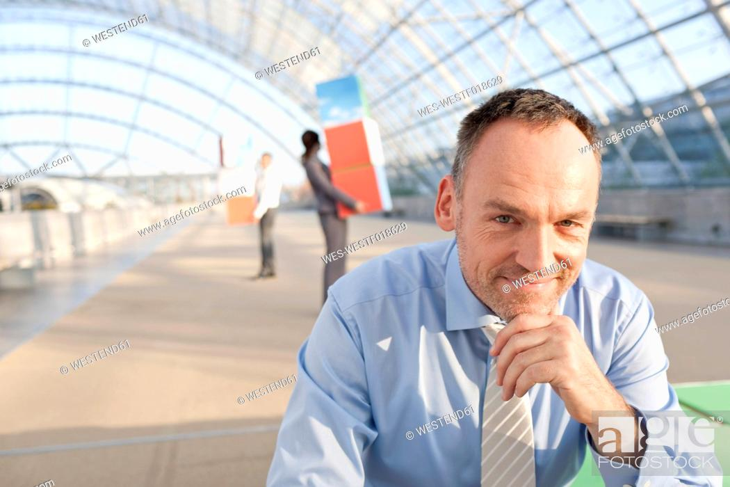 Stock Photo: Germany, Leipzig, Businessman smiling with business people in background.
