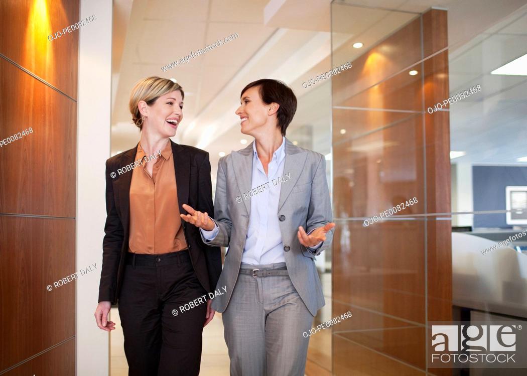 Stock Photo: Businesswomen talking and walking in office corridor.