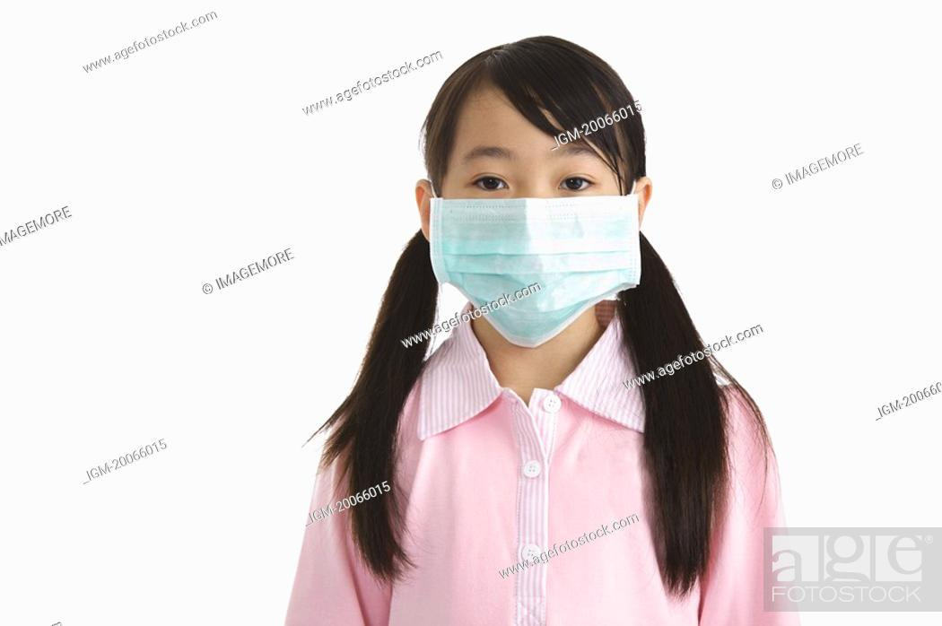 Stock Photo: Little girl wearing a surgical mask and looking at the camera.